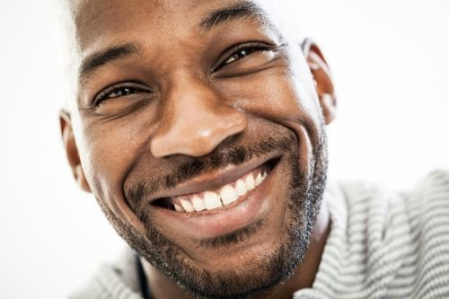 Close up portrait of a happy black man in his 20s isolated on a white background